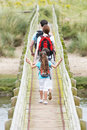 Rear View Of Family Walking Along Wooden Bridge Royalty Free Stock Photography - 33088557