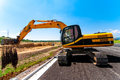 Full Utility Excavator Working On Side Of Road Construction Site Stock Photos - 33122503
