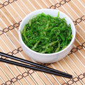 Seaweed With Sesame Seeds With Chopsticks In Ceramic Bowl On Bamboo Mat. Chuka Salad. Royalty Free Stock Photography - 33153417