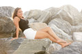 Woman Sitting On The Rocks Royalty Free Stock Images - 33176049