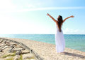Woman Relaxing At The Beach With Arms Open Enjoying Her Freedom Royalty Free Stock Photo - 33272305