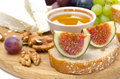 Cheese, Bread, Figs, Grapes, Honey And Nuts On Wooden Board Stock Photos - 33281683