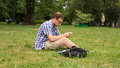 Young Man With Mobile Phone Sitting On A Grass. Royalty Free Stock Images - 33368469