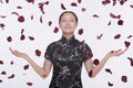Woman In Traditional Clothing And Arms Outstretched With Rose Petals Coming Down Around Her In Mid Air, Studio Shot Royalty Free Stock Image - 33397606