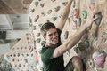 Smiling Young Man Climbing Up A Climbing Wall In An Indoor Climbing Gym Royalty Free Stock Images - 33401479