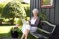 Elder Woman Reading Newspaper In Backyard Garden Stock Photo - 33522210