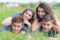 Four Happy Friends Lying Together On Green Grass Outdoors Royalty Free Stock Images - 33552629
