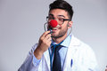 Young Doctor With Clown Red Nose Listens To Himself Stock Photography - 33657832