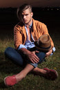Casual Man Sitting With Hat On Knee Royalty Free Stock Photos - 33658908