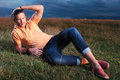 Casual Man Laying In The Grass And Fixing His Hair Stock Photo - 33659100
