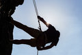 Silhouetted Man Climbing Rock Stock Photography - 33671582