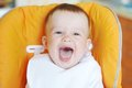 Laughing Baby In Bib Sits On Baby Chair Royalty Free Stock Photography - 33872787