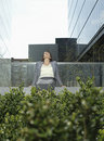 Businesswoman Relaxing On Wall Outside Office Buildings Stock Photography - 33895172