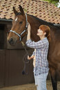 Woman With Horse Outside Stable Royalty Free Stock Photos - 33902148