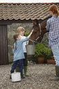 Mother And Kids Feeding Horse Outside Stable Royalty Free Stock Photos - 33908478