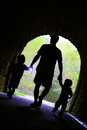 Father And Children Exploring Dark Tunnel Stock Images - 33923624