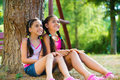 Hispanic Sisters Sitting Under The Tree And Talking Stock Images - 33982764