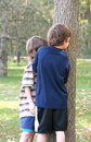 Boys Peeking Around Tree Royalty Free Stock Photo - 3408045