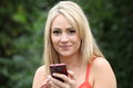 Smiling Blond Woman With A Mobile Phone Royalty Free Stock Photos - 34056038