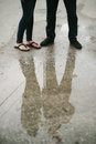 Couple Standing On Street Reflection In Water. Royalty Free Stock Image - 34211016