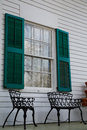 Wrought Iron Benches Under Green Shutters Stock Photos - 34307953