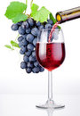 Pouring A Glass Of Red Wine And Bunch Of Grapes With Leaves Royalty Free Stock Photos - 34321798