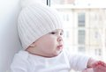 Baby Sits At A Window Overlooking The Next House Royalty Free Stock Photo - 34329545