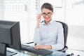 Charming Classy Brown Haired Businesswoman Looking At Camera Over Her Glasses Royalty Free Stock Images - 34398529