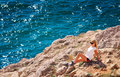 Young Woman Relaxing On Rocky Cliff With Blue Sea On Background Stock Photo - 34598170