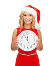 Woman In Santa Helper Hat With Clock Showing 12 Royalty Free Stock Images - 34602469