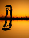 In Lover Reflection Of Man And Woman Holding Umbrella In Evening Sunset Silhouette Royalty Free Stock Photos - 34745628