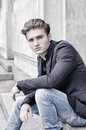 Attractive Blond Young Man Sitting Outdoors Stock Images - 34873154