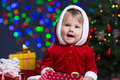 Baby Girl Dressed As Santa Claus At Christmas Tree Royalty Free Stock Image - 34882006