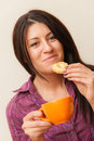 Girl Eating Cookie And Drinking Coffee Royalty Free Stock Photography - 34918367