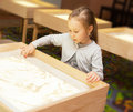 Girl Draws With Sand On A Light Table Stock Photo - 34980670