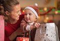 Happy Mother And Baby Checking Christmas Shopping Bags Royalty Free Stock Photos - 35020138