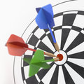 Red, Green And Blue Darts Sticking In Dart Board Royalty Free Stock Photography - 35053357