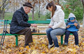 Cute Young Boy Sitting On A Park Bench Holding A Tablet Computer While His Mother And Grandfather Play Chess Stock Photography - 35104442