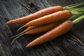 Raw Organic Carrots With Greens On Wood Stock Photos - 35148213
