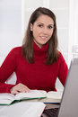 Reading And Research: Brunette Woman Sitting In Red Jumper At De Stock Image - 35183051