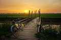Bicycle On Wooden Fence Of Bridge At Sunset Royalty Free Stock Photo - 35327125