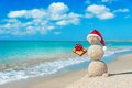 Smiley Sandy Snowman At Beach In Christmas Hat With Golden Gift. Stock Photography - 35363442