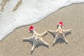 Sea-stars Couple In Santa Hats On The Sand. Royalty Free Stock Image - 35363476