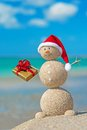 Smiley Sandy Snowman At Beach In Christmas Hat With Golden Gift. Royalty Free Stock Images - 35363809