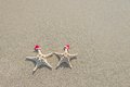 Sea-stars Couple In Santa Hats On The Sand. Stock Photography - 35363862
