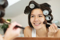 Woman In Curlers Applying Makeup Royalty Free Stock Image - 35364496