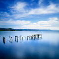 Wooden Pier Or Jetty Remains On A Blue Lake. Long Exposure. Royalty Free Stock Image - 35390526