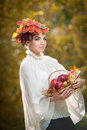 Autumn Woman. Beautiful Creative Makeup And Hair Style In Outdoor Shoot . Girl With Leaves In Hair Holding A Basket With Apples Stock Image - 35454661