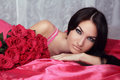 Beauty Portrait Of Brunette Girl With Red Roses Lying On The Bed Stock Image - 35595921