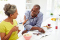 Couple Having Breakfast And Reading Magazine In Kitchen Stock Images - 35612724